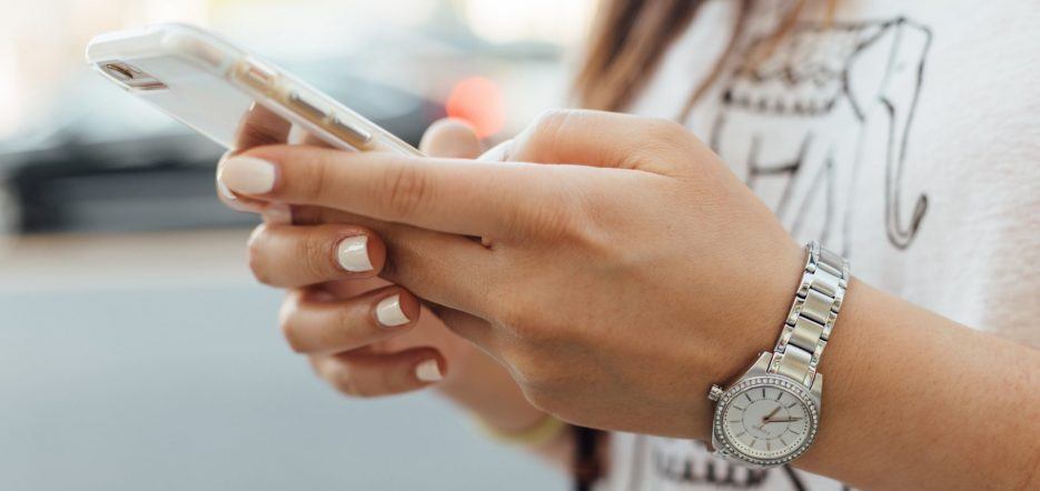 Damenhände die am Handy drücken
