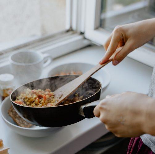 Eine Dame die aus einer Pfanne essen auf Teller aufteilt