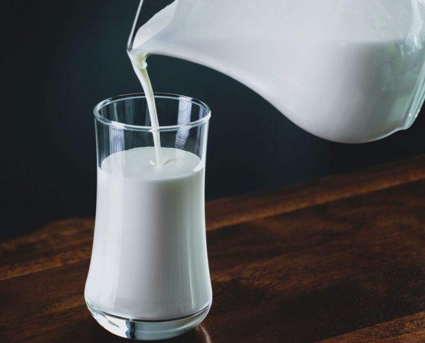 Ein Glas Milch das gerade befühlt wird