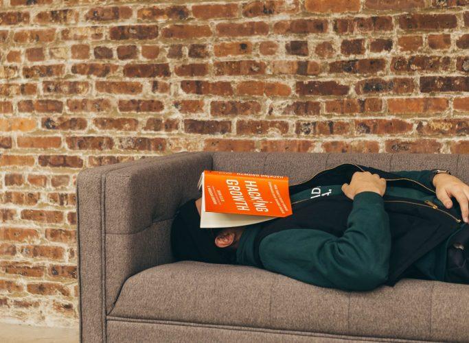 Ein Mann schläft auf einer Couch und hat ein Buch auf seinen Kopf