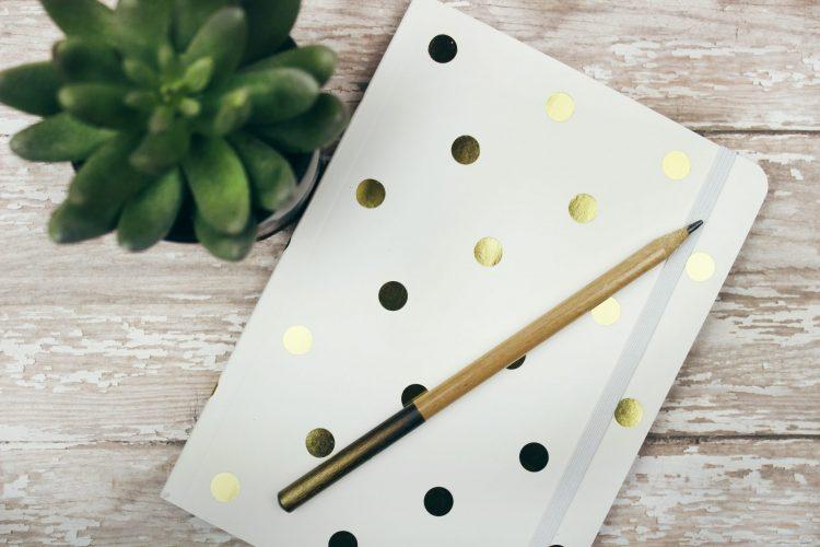 Weisses Notizbuch mit goldnen Punkten
