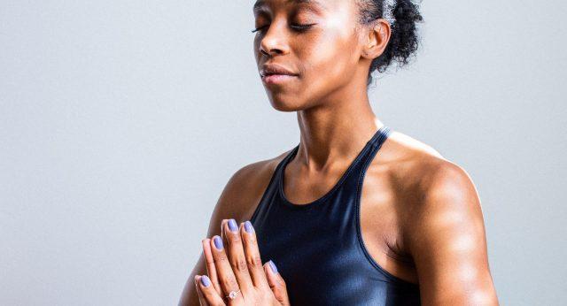 Eine Dame die ihre Hände vor ihrer Brust faltet