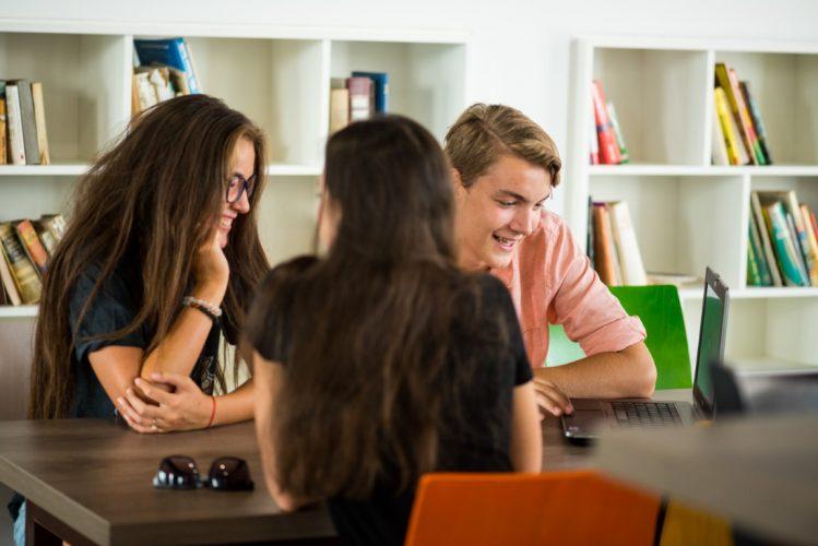 Zwei Frauen und ein Mann sitzen am Tisch vor einem Laptop