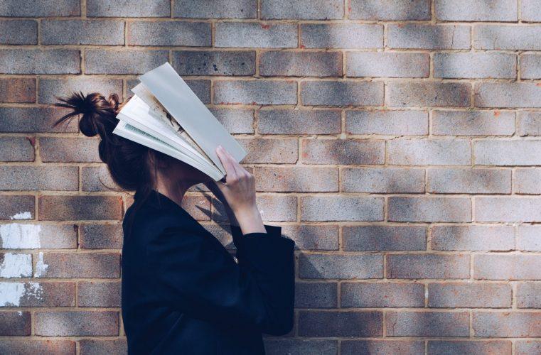Eine Studentin hält ein Buch vor ihren Kopf
